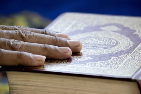 The hands of people who have faith placed on the books of Islam. Muslims believe in the prophet and faith is the beginning of everything.
