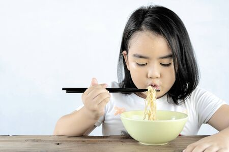 Asian girls are blowing instant noodles with a lot of appetite. With her sweat on the forehead, She looks cute and appetizing, a happy child. Banco de Imagens