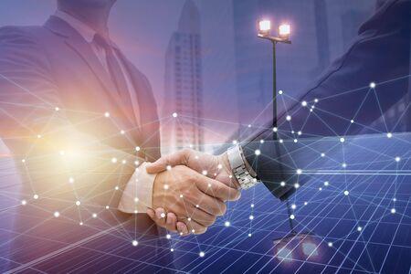 Biznesmeni podają sobie ręce na przedsięwzięcia biznesowe i marketing energii. W przyszłości potrzebne jest światło słoneczne. Panele słoneczne wymagają wiedzy w zakresie instalacji. Fotowoltaika dla sektora biznesowego.