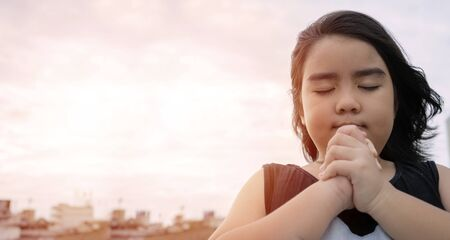 Little girl praying in the morning.Little asian girl hand praying,Hands folded in prayer concept for faith,spirituality and religion. Outdoor sky wide.