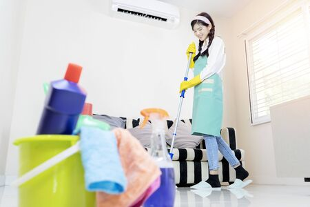 Cute housewife is mopping the floor with a mop.  Wear rubber gloves to protect chemicals. Cleaning equipment is placed.
