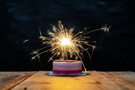 Success celebration concept. The cake on the table has a fireworks that illuminates the light and looks amazing.