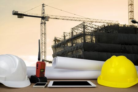 control concept. The construction of a large building, structure building with a crane was installed on, the front desks of the engineers, with helmet, Tablet, radio, schematic drawings placed. Stock fotó