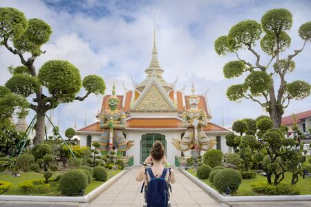 European tourists are taking pictures. Giants front of the church at Wat Arun. Bangkok - photo of one the temples gates with the gigantic guardians protecting it. Buddhist temple in Bangkok,Thailand.