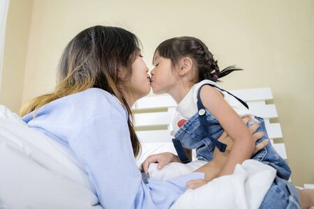 Las mujeres asiáticas, de cara bonita, su hermana y su hermana se ata mucho, muestran su amor besándose, estaban sentadas en la cama. Foto de archivo