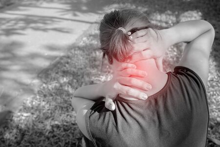 Neck pain during training. woman runner with sport injury in sports bra rubbing and touching upper back muscles outside after exercise workout in summer. She has a lot of pain. Stok Fotoğraf - 130386216