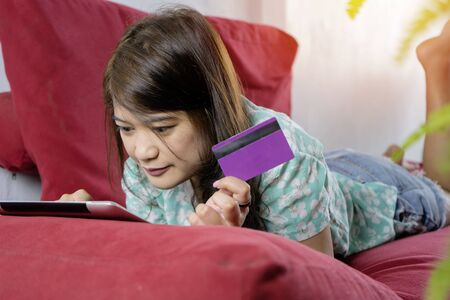 Buy online concept. Women are using tablets to shop online. By paying by credit card for convenience and speed, She lay on a red sofa at home.