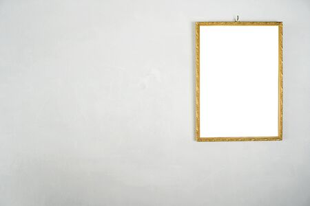 Golden picture frame hanging on a white cement wall.  White label floor for text, images, advertising media.