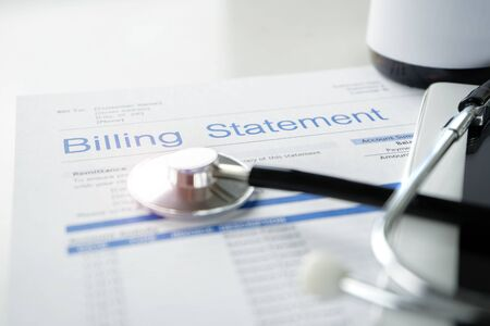 Health care billing statement with stethoscope, bottle of medicine for doctors work in medical center stone background.
