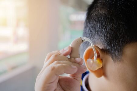 Use hearing aid cocept for people with hearing problems. The child is wearing a hearing aid to help make his lifestyle easier. Imagens
