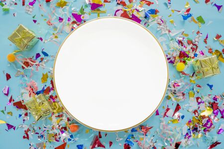 Celebrate success concept. A white circular dish placed in the middle, colorful scraps of cellophane and a golden gift box. The festival party appreciated success.