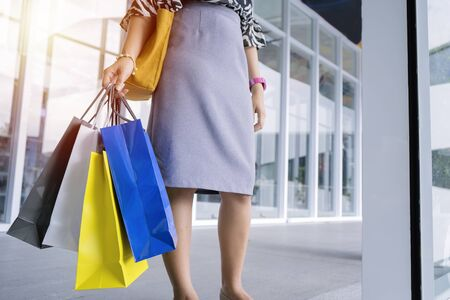 Shopping concept. A woman standing carrying a colorful paper bag obtained from shopping. She is happily traveling back to buy the things she needs.