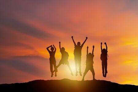 Humano exitoso y espíritu de lucha, grupo de silueta joven, la gente está encantada con levantar la mano más alto. triunfar. Concepto de negocio, éxito, logro, trabajo en equipo y objetivo.