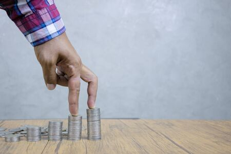 Systematic financial investments concept, and continuous gains, compared to stair steps. Business people use their fingers to walk up a pile of coins.