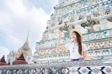 Asian woman tourist is traveling and sightseeing inside Wat Arun temple in Bangkok, She is raising her hand to greet her friend.