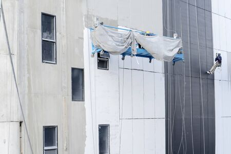 The painter is working to paint the building. By using scaffolding for work and abseiling. There is a risk that the cause of the accident must be very careful when working.