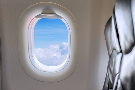 Window View From Passenger Seat On Commercial Airplane. Beautiful view from the window of airplane to blue sky with white clouds at height in sunny day from the passenger seat. Stock Photo