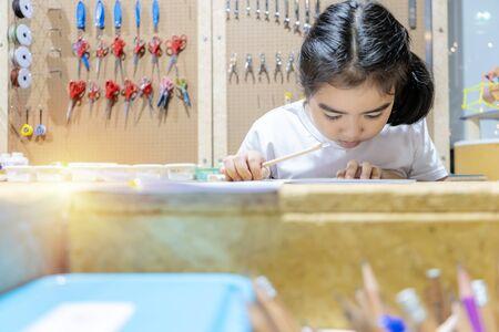 Ein süßes Mädchen beabsichtigt, im Klassenzimmer zu lernen. Sie entwirft, experimentiert und erzielt Ergebnisse. Es gibt viele Geräte, die zum Lernen verwendet werden können.