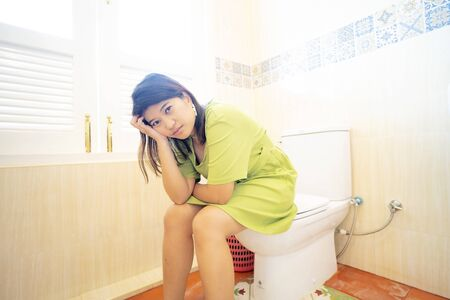 Asian young woman suffering from constipation on toilet bowl at home, sitting on toilet defecating.