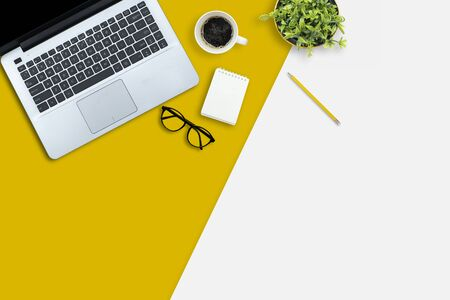 Top view of the desk concept. The Contrasting colors, white and yellow desk is equipped with work equipment, notebooks, laptops, coffee cups, pencils, potted plants, glasses.