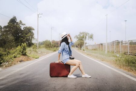 Cute Asian woman. She is traveling in Thailand, she is sitting on a vintage suitcase placed in the middle of the road. Stok Fotoğraf
