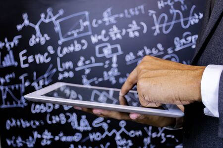 Close to the hand of the teacher using a tablet, Background is blackboard with a lot of mathematical formulas, The characters are glowing. Banco de Imagens