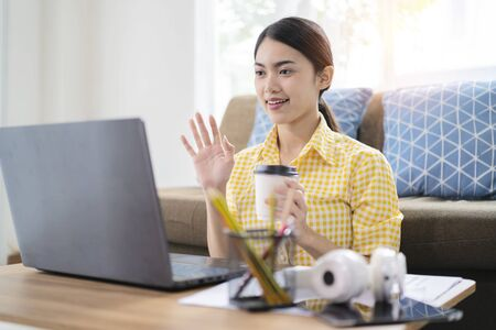 Working form home concept. An Asian woman conducts an online meeting, Which she has used via a tablet Stock Photo