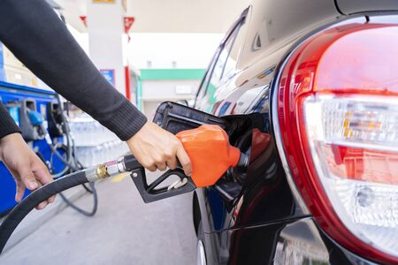 Refuel cars at the fuel pump. The driver hands, refuel and pump the car's gasoline with fuel at the petrol station. Car refueling at a gas station Gas station