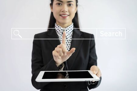 search concept. An Asian businesswoman is using a tablet. Use your finger to touch the screen to search. 免版税图像