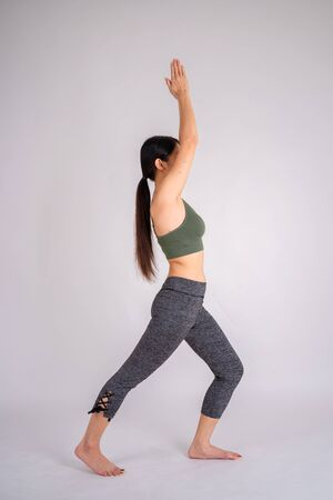 Side view portrait of beautiful Asian woman wearing a tank top. Gray isolated background. doing yoga or pilates exercise. Standing in Warrior one pose, Virabhadrasana Stock Photo