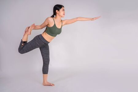 A beautiful Asian woman practicing yoga. Wellness concept. Calmness and relax, woman happiness. Toned picture, Gray isolated background Stock fotó