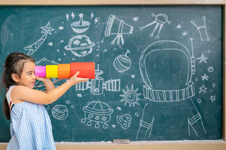 Education concept, The story in the universe is a mystery, I need the answer To make progress, Asian girls in front of the space station in hand Binoculars made of paper.