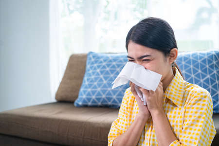 Flu. Young woman got nose allergy, flu sneezing nose sitting at the her house. She is allergic to air from dust.