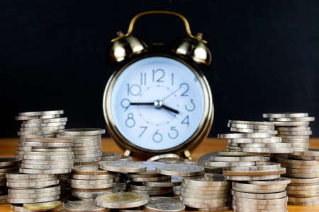 Alarm clock and step of coins stacks on working table, time for savings money concept, banking and business idea. Imagens