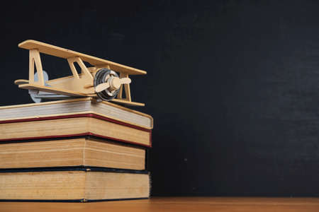 The books that are stacked and Plane model placed on the table. The background is a blackboard, Back to school concept.