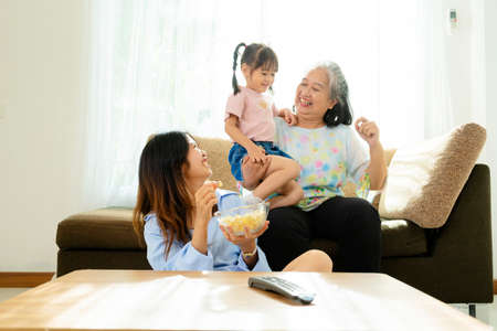 Three age ranges, Asian niece and grandma enjoying watching movies and eating popcorn in the living room in the house Standard-Bild