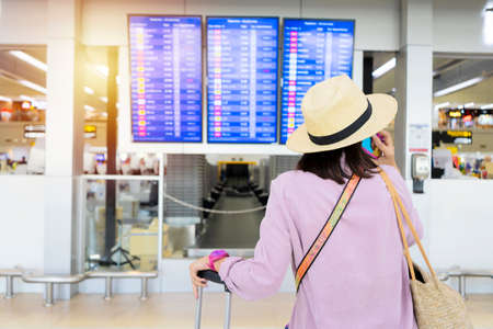 Young elegant tourist with hand luggage in international airport terminal, looking at information board, checking her flight. Cabin crew member with suitcase.