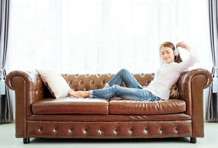 Asian women are happily sitting on the leather sofa in the living room, listening to music with headphones.