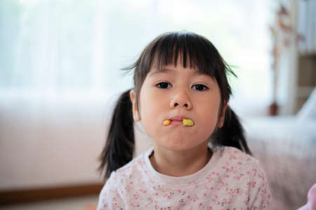 An Asian girl uses her mouth to hold the biscuits. Playing as the fangs sticking out