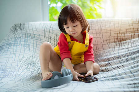 child girl happy look smart phone. asian child. Child development, technology and lifestyle concept