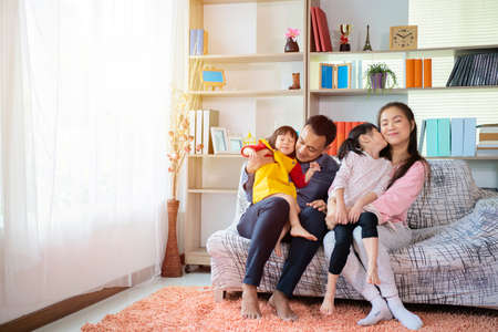 Happy Asian family hugging and cuddling with two little daughters, sitting on cozy sofa at home, smiling parents and preschool children having fun together, family enjoying free time
