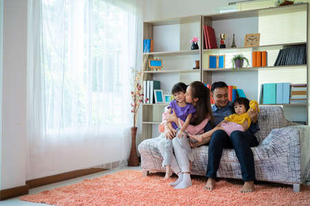 Happy Asian family playing together at sofa in home living room, the image of a happy Asian family laughing on couch