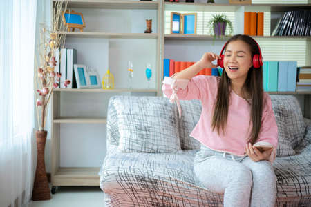 Asian woman with headphones relaxing at home late at daytime, she is lying on the armchair and listening to music using a smartphone Imagens