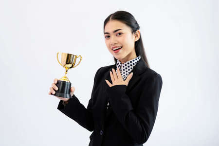 Successful young asian woman holding a trophy on white background. Woman with a golden cup concept Imagens