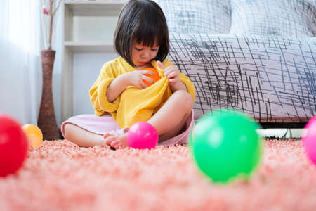 A cute Asian girl is happily playing colorful multicolor ballistic ball in the living room at home, putting the ball into her shirt. Imagens