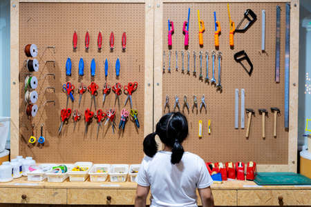 Girl is choosing  tools on the table and board. Glue, tape measure, steel ruler, screwdriver, wrench, scotch tape, yarn, scissors, hammer, cutter, orderly hanging, ready to use. Workshop scene concept