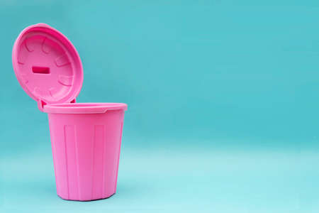 A pink mock-up trash can with an open lid and it is open on a blue background. There is a blank space to insert text Standard-Bild