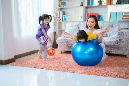 A mother, two Asian daughters, happily playing at home, mother and daughter smiles, they are with a big wind ball.
