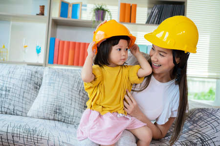 An Asian mother and daughter play as an engineer in command, with yellow helmet as role-playing equipment. Standard-Bild