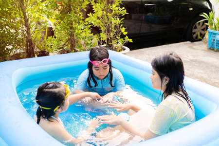 An Asian family is playing in an inflatable pool. By having fun playing, blowing, blowing soap. Love and warmth for each other in the family.